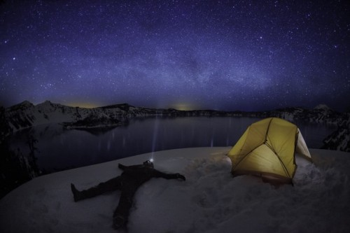 "lickypickysticky:  Ben Canales star gazing at Crater Lake: Here on my first time visit to Crater Lake National Park, I wanted to  leave with an image that I could look back on and remember the  experience. I was with a friend taking pictures also, and before I took  the picture, I called over to him and said, ""Hey man, watch this!"" With a  laugh, I spread my arms out and fell backwards into the snow. A second  later, the camera timer clicked the shutter and the long exposure began.  After the shutter clicked back closed, I stayed on the ground for a  good while staring up mesmerized by all the sparkling stars overhead."