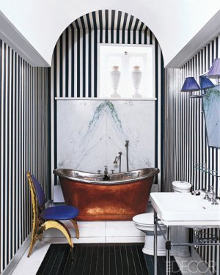 Chic and graphic stripes painted on the bathroom walls at a couple's   apartment in Paris draw the eye upward to the rounded arch. The  nickel-and-brass tub dates from the 19th century, and the chair by  Honoré Paris is from Galerie Yves Gastou. Photographer: Roger Davies