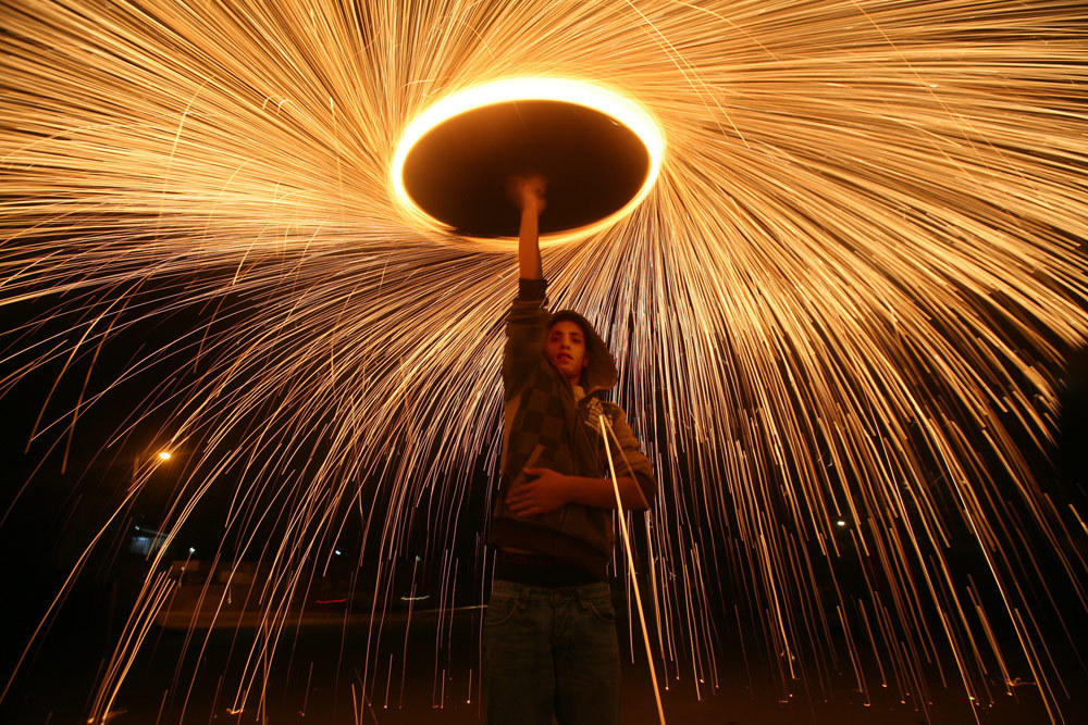 aljazeera:  A Palestinian boy in Gaza City plays with fireworks to celebrate the beginning of Ramadan [Ali Ali/EPA]