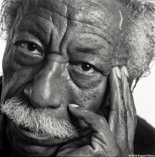 "Gordon Parks (1912 -2006) He was stillborn — no heartbeat, declared dead by the family doctor, and put aside for later burial. Another doctor in the delivery room had an idea, and immersed the newborn in ice-cold water. The shock caused his heart to start beating, and the baby was soon crying and healthy, and named for Dr. Gordon, who had saved his life. In the more than ninety years of his life, Gordon Parks became internationally renowned as a photographer, filmmaker, poet, novelist, and composer. Parks grew up poor in Fort Scott, Kansas, the youngest of 15 children. One of his early memories was hearing his all-black class told by their white schoolteacher, ""You'll all wind up porters and maids."" His mother died when Parks was 14, and he was sent to live with an older sister in Minneapolis, until her husband kicked him out. Between bouts of homelessness, he earned rent as a piano player in a bordello. He also worked as a busboy, a Civilian Conservation Corpsman, and as his teacher had predicted, as a porter and later waiter on the transcontinental North Coast Limited. At 25, he bought a used camera for $7.50 and began working as a self-taught freelance photographer, focusing on everything from fashion to the effects the depression in Chicago's slums. By 1944, he was the only black photographer working for Vogue, and in 1948 he became the first black photographer at Life, the most prestigious magazine of its day for photography. Eventually Life sent him to France, Italy, and Spain, and stateside he became known for his photos documenting the civil rights movement. He reported on segregation in Alabama in 1956, the growing Nation of Islam movement in the 1960s, and the assassination of Martin Luther King. In his spare time, Parks also directed a few films."