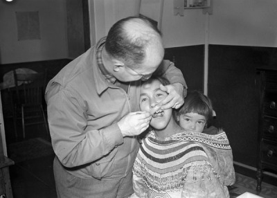 Inuit woman getting her teeth examined. 1945.  Note her baby in her hood. Inuit women wore parkas that had hoods large enough to fit an infant if needed. This kept the babies close to their body, and wrapped in warm material, without having to make a separate papoose or harness to carry their baby in.  Inuit woman in the Northwest Territories. 1906. From the Library of Congress Lomen Bros. Collection.
