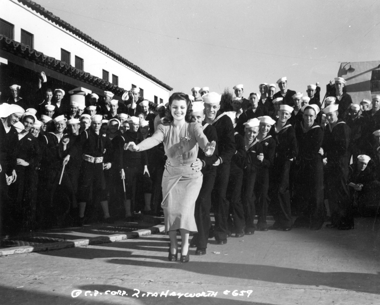 lovefortheold:  Rita Hayworth leading the sailor congo.  Lucky Rita!