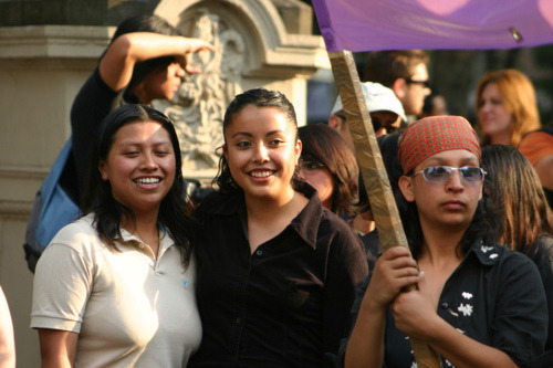 Two women stand, one with her arm around the other, smiling. Next to them is another woman with a more serious facial expression, carrying one edge of a banner.