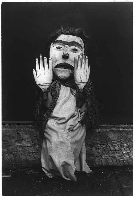 "Kwakiutl person wearing an oversize mask and hands representing a forest spirit, Nuhlimkilaka, (""bringer of confusion"")."
