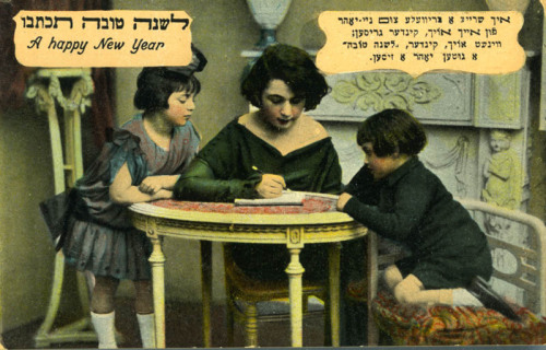 "IT'S NEVER TO EARLY TO START SENDING OUT YOUR GREETING CARDS! CHAG SAMEACH! Sending out ""Happy New Years"" cards around Rosh Hashana is great way to show you care. Have you written yours yet? You can even try to get the kids involved, like the woman in this picture, and start teaching them early the etiquette of Judaism. Woman sitting and writing at a table. Two children stand next to her. Divided back.  #125. Yeshiva University Museum, New York (2005.039)"