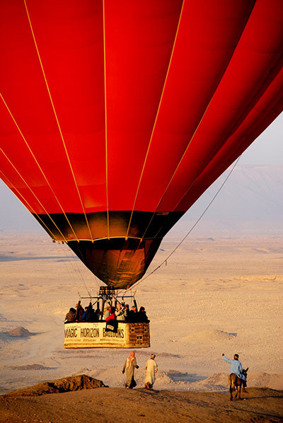 "fattysaid:  Touch down, Luxor, Egypt ""As soon as the balloons came close to landing the local children started following them. The juxtaposition of ancient animal transport and modern tourist balloon a few feet away was too good to miss. It was an awkward shot as I was in a balloon myself, but for a second or two everything was in the right position.""  By: Andrew Kerr"