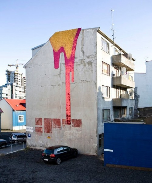 rustybreak:  Theresa Himmer.The relationship between street art and buildings isn't always happy, sometimes resembling an unhappily-arranged marriage, with only a brief courtship occurring in the middle of the night. But this week, I thought we could look at some happier unions between street art and buildings. Using a kind of sequins for buildings to makes images of glaciers and lava, much of the original wall's surface is visible. These glittery additions are bright spots in the grey urban fabric and probably a god-send during the winter months when the capital city gets just a few hours of daylight. So maybe a street artist working under the cover of dark would have more hours to work in Reykjavik, but the scale and technical construction that went into these hints at a longer and more symbiotic planning phase.