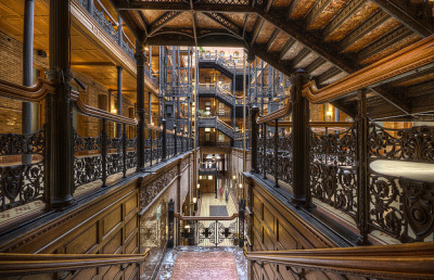 fuckyescalifornia:  The Bradbury Building, built in 1893 is considered as one of the finest architectural masterpieces in Southern California. The dramatic central court made of glazed brick walls, ornamental cast iron made in France, tiling, stairs of Belgian marble and polished wood railings is flooded in the light from the huge skylight five stories above. | Los Angeles, California by Neil Kremer  I feel like watching 500 Days of Summer…