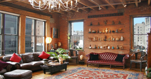 brick walls with pottery on shelves; open floor & big windows