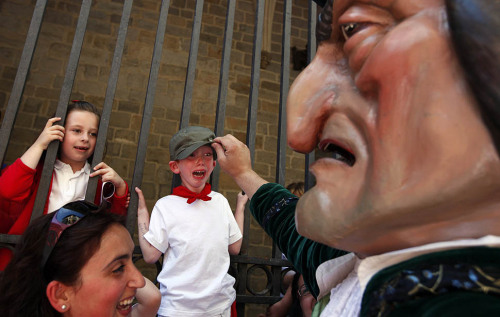 Pamplona, Spain — A boy reacts in fear as an enormous puppet lifts up his hat during a parade of costumed characters. (via)  LMFAO—-poor little boy!