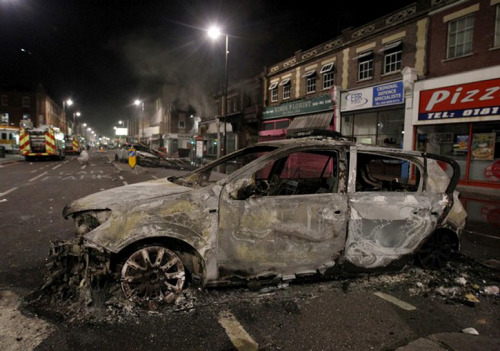A burnt police car is seen on a street in Tottenham, north London August 7, 2011. Crowds attacked riot police and set two squad cars alight in north London on Saturday following a protest at the fatal shooting of a man by armed officers earlier in the week.
