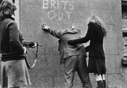 Two female IRA members patting down a man - 1970's