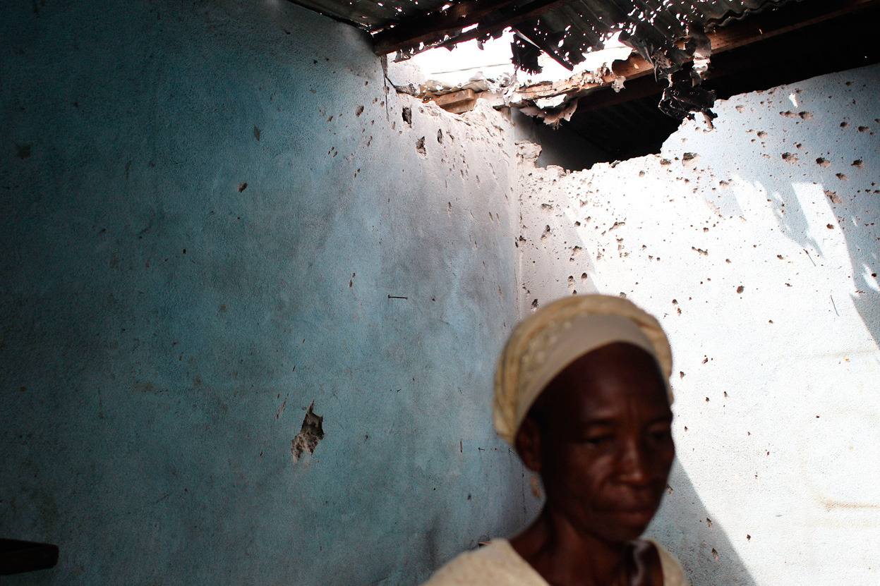 Karidja Cisse walks through her kitchen, damaged by a mortar during a Saturday bombardment by government forces, in the PK18 area of Abobo, Abidjan, Ivory Coast, Wednesday, March 2, 2011.  #15