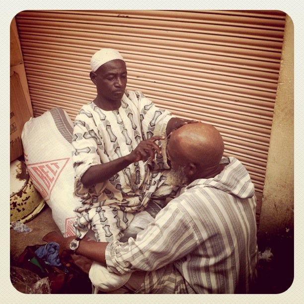 "Occupation in GhanaA ""mobile"" barber in action at Makola Market. Based on how he is dressed, he might be a Muslim from the Northern region. Photo Credit: intermsofme"