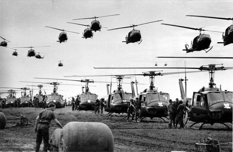 In this 1966 file photo, U.S. Army helicopters providing support for U.S. ground troops fly into a staging area fifty miles northeast of Saigon, Vietnam. (AP Photo/Henri Huet)