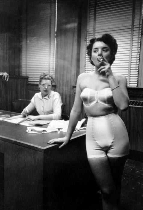 Lingerie model smoking in an office (from 'Chicago: City of Contrasts')Photograph by Stanley Kubrick, Chicago, 1949