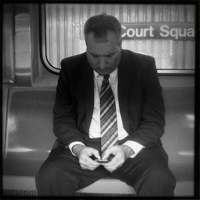 businessman texting. 7 train @ court square. on Flickr.This is a shot I snapped on the 7 train yesterday morning of a businessman texting as the train approached Court Square. The station was formerly known as 45th Road/Courthouse Square, but now with a big fancy connection to the E, M, and G lines, the station has been renamed for simplicity's sake. Hope he got his text in, since the train dips underground after this stop!