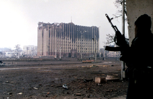 A Chechen rebel looks towards the ruins of the Presidential palace in Grozny, Chechnya.  The Palace was demolished by Russian troops a year later.   January, 1995.