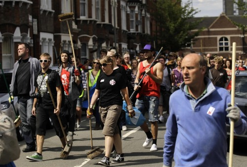 SWORDS INTO BROOMSTICKS    Londoners walk with brooms en route to help clean up after rioting  that took place the previous night outside Clapham Junction railway  station in Battersea, London, Tuesday, Aug. 9.  (Photo: Matt Dunham / AP via MSNBC.com)