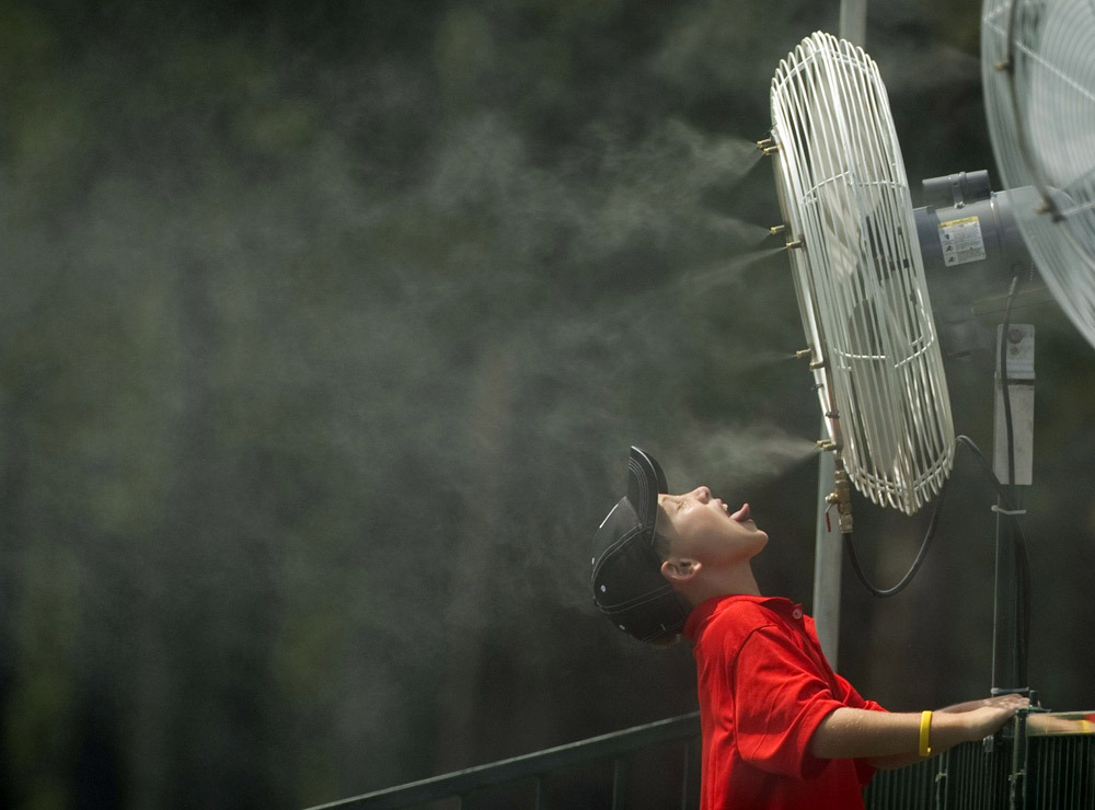 npsports:  Rising temperatures in Hotlanta A boy tries to stay cool in a mist-blowing fan near the 18th green during a practice round of the 2011 PGA Championship Tournament at Atlanta Athletic Club. Photo: Don Emmert/AFP/Getty Images