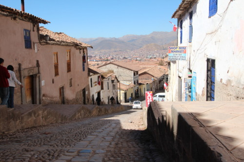 "Day 3: Cusco, Peru. In hopes of a view many don't get to experience, this image birthed about 4 or 5 blocks uphill from Plaza de San Francisco. If you must walk the length of this street, carry little. This day, my amigos from Houston and Durango arrived in Cusco. Union of the team could not have come at a more confusing time, as the originally planned hotel had no reservation for the group. Rather, our names had no ink on the list of reservations for either of the nights. I checked…3 times in 24 hours. Doing what I could to avoid the bears of internet and the haunting on-button of my mobile phone, I strolled the streets for two hours looking for my fellow adventurers. Thinking ahead, we concluded a preset time, in fear of not finding each other, we would turn on our phones and shoot for the verbal contact. Yes, I called a Houston phone number from a Dallas number in Cusco, Peru. After a moment of Angry Elf-dom, I harnessed my packs on to my determined self and step after step paced my way up a hill to the base camp hostel my team occupied, post call. Did I mention AT&T greeted my phone's startup with a $19.97/mb reminder? Oh, ""Domestic data rate does NOT apply in this location."" Thanks AT&T, I gathered that much. This picture view down on the town/city of Cusco from Hostel Loko."