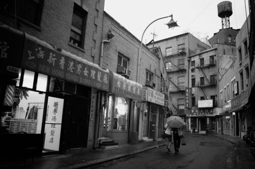"A rainy evening in Chinatown, New York City.   There is nothing like a rainy evening in New York City. The streets, darkened by the rainfall take on a beautiful sheen while walls and storefronts glisten. Couples huddle under shared umbrellas and inviting scents of dinner fill the streets.   This is one of my favorite spots on rainy evenings like the one in this photo. It's here where my favorite hand-pulled noodle restaurant resides just round the bend (aptly called Tasty Hand-Pulled Noodles). After drying off and sipping hot jasmine tea, some of the most comforting and inviting food in Chinatown arrives at the table while the rain-drenched streets wait patiently outside.     —-  View this photo larger and on black on my Google Plus page  —-   Buy ""Chinatown in the Rain "" Posters and Prints here, View my store, email me, or ask for help."