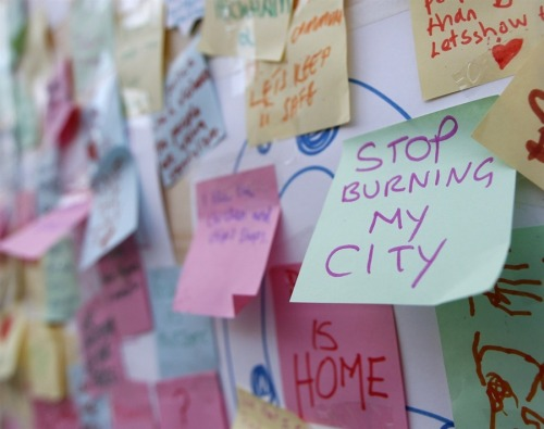 "PLEA   Hundreds  of messages of support from the community of Peckham are seen posted on  a looted storefront in the south London district on August 10. The city was generally calmer Tuesday evening; police are investigating the deaths of three men in Birmingham who were struck by a vehicle while the men were trying to ""defend their neighborhood.""  (Photo: Chris Helgren / Reuters via MSNBC.com)"