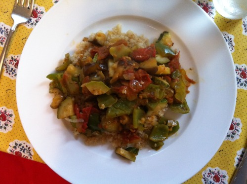 "Ratatouille Caroline Tracey makes a classic dish with the Farm's freshest ingredients and no recipe to guide her.  At the start of this summer's farm internship, I planted the seeds of vegetables that would be bountiful late in the summer in specific anticipation of one dish: ratatouille. I waited for the day when tomatoes, eggplants, zucchini and onions would be ready to be picked from their plants and simmered all together. Much of the farm conversation this summer has revolved around we interns' food-challenged backgrounds. Most of us grew up eating fast food and so working for the YSFP, with its focus on the way that food brings people together, felt like jumping blindly into something that other people held innately, or had inherited effortlessly, from childhood. Growing up in a house that was always down a stove burner or three, my family's food traditions included ordering pizza weekly with my grandmother and going to Applebee's with my grandfather (proud owner of man's simplest palette). Family gatherings were not lacking in tradition or celebration – we're jovial people – but in my mind's eye, it's Parcheesi on the dining room table, not a home-cooked meal. Learning to make ratatouille opened to me the world of making delicious things out of vegetables, and having ownership and self-sufficiency in the kitchen. Unsurprisingly, the catalyst in this story is the movie of the same title. I was spending the weekend at my Dad's house while the movie was in theaters, and my stepmother, who is committed to orchestrating family outings during the sparse time that we all spend together, suggested that we go see it. It's a hard task to get my claustrophobic father into a theater, but she did, and afterwards got him into the kitchen to prepare, from memory, this dish that I had never heard of. It turned out that he had learned to make the French peasant dish in the years after high school that he spent living in towns in France and Spain. I joined him in the kitchen, and he started to pass the method on to me. Yesterday, I got to re-create it here for the first time this season. The tools for making ratatouille are simple: a knife and a pan large enough to be loaded up with cut vegetables. Clean-up is easy! To prepare my working space, I lined up my vegetables on the counter: onions, zucchini, eggplants, peppers, and tomatoes – a set that always looks like it should be photographed. First into the pan go the onions. I used three of the small white ones we pulled up from the farm this week. After peeling them and warming up the olive oil in the pan, I hold each onion in my hand and cut carefully through it towards my thumb, making odd shapes – the peasant lore says that more surface area means more flavor. I let the onions simmer, turn the heat low so that nothing will cook too quickly, and add the zucchini, cutting it with the same irregularity as the onions. I let the two cook over the low heat, and cover the pan with a sheet of tin foil. The tin foil to retain moisture is an invention of my dad's. Everyone adds their own techniques to ratatouille - as Dad taught me the dish, he reminded me, ""there's no recipe, so you'll do it a little differently every time, and eventually you'll figure out your own ways."" By now I have made the dish enough times that when I make it, I recall the method he taught me, but also consider what sounds right to me – getting closer each time to a dish that is distinctly mine. When the zucchini gets a little brown, I add the eggplants (three small ones from the farm), cutting with the same technique as the other vegetables. In the movie, the vegetables are served in perfect thin slices – this dish will look nothing like that, and will be better for it! The eggplants get soft and brown quicker than the zukes. As they do, I stir the vegetables around a bit, and add some more olive oil and some spices – thyme, oregano, salt and pepper, to my tastes, one example of the decisions that make the dish one's own. A little sugar is also important – it cuts the acidity of the tomatoes. At this point in the recipe one can add some wine or beer for extra liquid, but not having any on hand, I relied on the juices of the vegetables. Next are the peppers, the only vegetables last night not to come from the Yale Farm. The only peppers I could find at the farmers' market were green ones from Stone Gardens farm, which are not as flavorful as their red and yellow counterparts, but I'll look forward to those later in the season. I core the peppers with a knife, pour out the seeds, and then tear off pieces into the pan. I move the vegetables around a bit with my spatula and prepare for the last addition to the dish: tomatoes, the most-anticipated jewels of the farm's season. I cored the tomatoes and cut off their worst blemishes – they are imperfect but sublimely so, the best badge to show that this meal had not come from anything close to industrial agriculture. Then I palmed the base of each and squeezed its juice into the pan, shielding with my other hand to try to minimize the number of errant seeds that landed on my shirt. With the new juice the dish starts to simmer audibly and the colors and flavors start to run together – my favorite part of making the meal. I rip up the rest of the tomatoes and add them to the mix. I add some more spices, stir the vegetables around a bit, and re-cover the pan with tin foil. The longer it simmers all together, the more the flavors will blend, and the better it will be. Voila! The most flexible of dishes, and one of the simplest and most delicious. From here you have lots of options for making the dish into a full meal. We elected last night to serve it on top of bulgur wheat; it's also great on pasta and rice. Once, in Georgia, I added okra and served it on grits; at home we often add black beans and make it into burritos. It can be anything and everything, and this time of year, all the ingredients are in season and delicious. Enjoy, and make it your own."