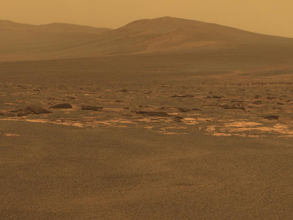 "At Last  A  portion of the west rim of Endeavour crater sweeps southward in this  color view from NASA's Mars Exploration Rover Opportunity. This crater  — with a diameter of about 24 miles (22 kilometers) — is more than 25  times wider than any that Opportunity has previously approached during  90 months on Mars. Endeavour crater has been the rover team's  destination for Opportunity since the rover finished exploring Victoria  crater in August 2008. Endeavour offers access to older geological  deposits than any Opportunity has seen before.  This view  combines exposures taken by Opportunity's panoramic camera on the  2,678th Martian day, or sol, of the rover's work on Mars (Aug. 6, 2011)  before driving on that sol. The subsequent Sol 2678 drive covered 246  feet (75.26 meters), more than half of the remaining distance to the rim  of the crater. Opportunity arrived at the rim during its next drive, on  Sol 2681 (Aug. 9, 2011). The closest of the distant ridges  visible along the Endeavour rim is informally named Solander Point, an  area that Opportunity may investigate in the future. The rover's first  destination on the rim, called Spirit Point in tribute to Opportunity's  now-inactive twin, is to the left (north) of this scene.  The  lighter-toned rocks closer to the rover in this view are similar to the  rocks Opportunity has driven over for most of the mission. However, the  darker-toned and rougher rocks just beyond that might be a different  type for Opportunity to investigate. The ground in the  foreground is covered with iron-rich spherules, nicknamed ""blueberries,""  which Opportunity has observed frequently since the first days after  landing. They are about 0.2 inch (5 millimeters) or more in diameter. This view combines images taken through three different filters,  admitting light with wavelengths centered at 753 nanometers (near  infrared), 535 nanometers (green) and 432 nanometers (violet). This  natural color is the rover team's best estimate of what the scene would  look like if humans were there and able to see it. Seams have been  eliminated from the sky portion of the mosaic to better simulate the  vista a person standing on Mars would see.  Image Credit: NASA/JPL-Caltech/Cornell/ASU"