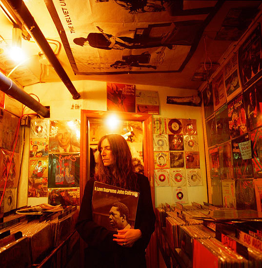 "Patti Smith in a record shop, New York City Photographed by: Danny Clinch Note the John Coltrane LP:""A love supreme"" between her arms and The Velvet Underground poster on the ceiling ! Danny Clinch @:http://www.dannyclinch.com"