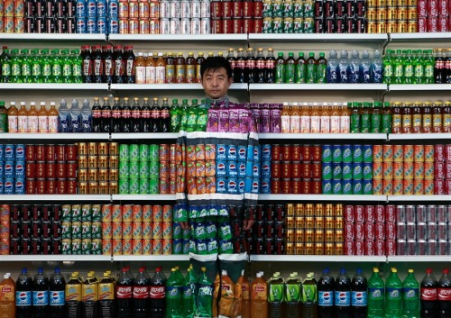 "msnbc:  Chinese artist Liu Bolin waits for his colleagues to put a finishing touch on him to blend into rows of soft drinks in his artwork entitled ""Plasticizer"" to express his speechlessness at use of plasticizer in food additives, in his studio at the 798 Art District in Beijing, China, Wednesday, Aug. 10, 2011. (AP) We've seen this guy in action before."