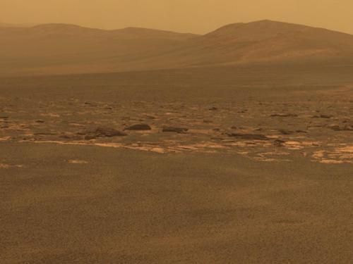 inothernews:  LONELY ISLAND  A portion of the west rim of Endeavour crater on Mars sweeps southward in this  color view from NASA's Mars Exploration Rover Opportunity.  The crater, with a diameter of about 14 miles, is more than 25  times wider than any that Opportunity has previously approached during  the rover's 90 months on Mars; it also has older geological deposits than any examined by the rover.  Opportunity had previously explored Victoria crater in August, 2008.  (Photo via NASA.gov)