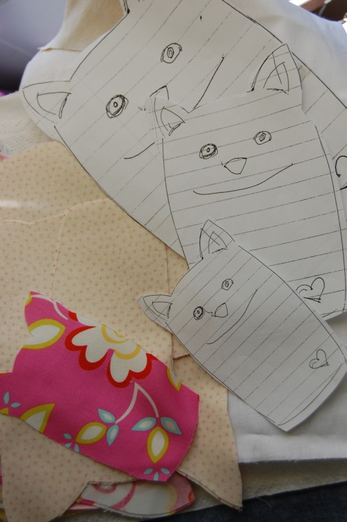 Working on kitty Stuffies… these are the patterns I drew, next to the ones I cut out of sweet floral fabric. Next steps are embroidering the faces and stitching on the hearts.