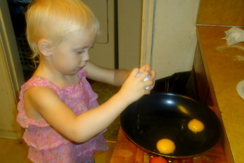 "Lydia was helping me make eggs for lunch. She is really good at cracking them and not getting any shell in the pan. I couldn't do that until I took a cooking class at school. She's only 2. Right after this picture, she cracked the 3rd egg and broke the yoke. She looked at me with a very disgusted look [if you know her, you know the look I'm talking about] and said ""Gross! That ones DEAD!"""