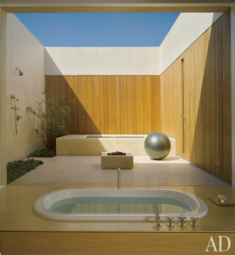 A Waterworks tub with Dornbracht fittings looks onto a courtyard featuring an outdoor shower, a hot tub, and a fire pit.