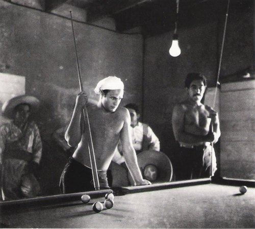 "Marlon Brando, Anthony Quinn in background. Taking a break from the shooting of ""Viva Zapata"". Photo by Sam Shaw 1952"