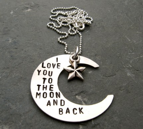 A crescent moon necklace. This crescent-shaped, sterling silver disc was hand-stamped with the text 'I LOVE YOU TO THE MOON AND BACK'. Accented with a star charm, this pendant comes on a sterling silver ball chain. Sold on Etsy.