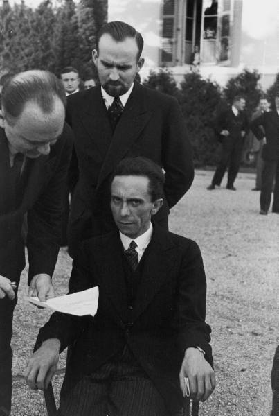 "Joseph Goebbels, Hitler's Propaganda Minister, 1933 in Geneva, by Alfred Eisenstaedt. ""I found him sitting alone at a folding table on the lawn of the hotel. I  photographed him from a distance without him being aware of it. As  documentary reportage, the picture may have some value: it suggests his  aloofness. Later I found him at the same table surrounded by aides and  bodyguards. Goebbels seemed so small, while his bodyguards were huge. I  walked up close and photographed Goebbels. It was horrible. He looked up  at me with an expression full of hate. The result, however, was a much  stronger photograph. There is no substitute for close personal contact  and involvement with a subject, no matter how unpleasant it may be."" (via Alfred Eisenstaedt on Getting Close in Street Photography — Eric Kim Street Photography)"