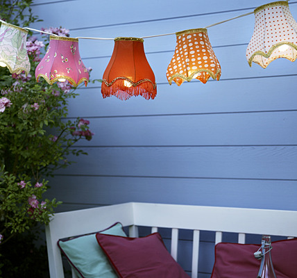 recycledfrockery:  Lamp Shade Lanterns - simple thrift store finds turned outdoor wonderland. All you need is a string of bulbs and some fantastic shades.