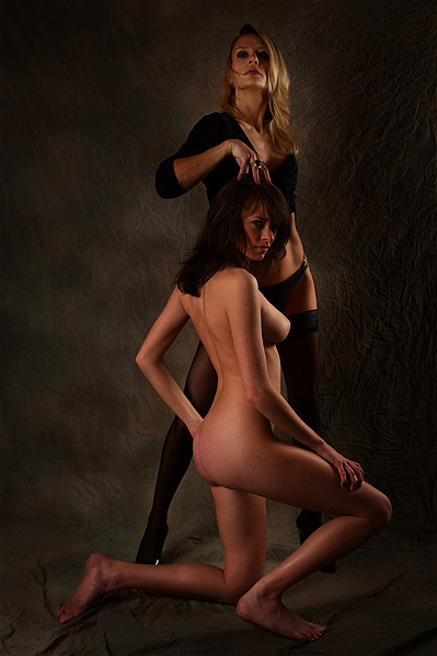 Mistress in high heels and stockings and her nude brunette pet