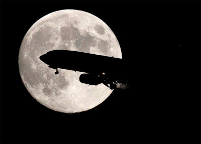 An airplane, landing at Boston Logan Airport, is silhouetted against the full moon in Boston, Massachusetts August 12, 2011. REUTERS/John Cetrino