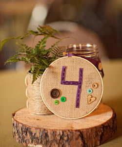 Absolutely LOVE this centerpiece with the buttons, burlap, and tree stump!! From the knot (number 8).