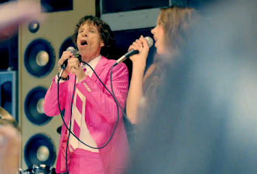 "Real men wear pink — and in the video for the debut single ""Miracle Worker"" from his supergroup, SuperHeavy, Mick Jagger is sure putting that adage to the test. While performing some voodoo magic, the dapper Jagger wriggles and writhes around in a hot pink suit with band members Joss Stone, Damian Marley and Dave Stewart backing him up. The Caribbean tinged cut plays well over the wacked-out dream the quintet have crafted. And it all comes together when the video culminates in a full-fledged concert scene with Jagger shimmying around while Stone belts it out. Check out behind the scenes photos and watch the video for SuperHeavy's ""Miracle Worker"" over at RollingStone.com —Colin Jones"