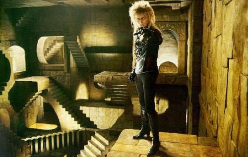 [Image is David Bowie as Jareth the Goblin King, standing in a room that resembles Escher's Relativity.  End description.] What're you doing, Bowie?  Not much, just hanging out in a fucking Escher painting.