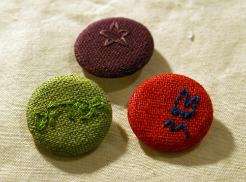Embroidered buttons! I've had a button maker for years, and magazine photos get boring.  I started making buttons out of fabric, then fabric I've screen printed, and now fabric I've both dyed and embroidered! The material was dyed [by me] during my summer course: the green is marigold and indigo (natural dyes), while the purple and red are reactive dyes (all on silk-ramie fabric).  The thread used for embroidery I did not dye, as the thread I DID dye is very sparse, and for now I'm saving it.(Not sure if it's clear to those unfamiliar with it, but the red button is embroidered with a grumpy-monster face I've been drawing/doodling for almost a decade.) And for non-Nerdfighters (or should I say, pre-Nerdfighters): DFTBA.