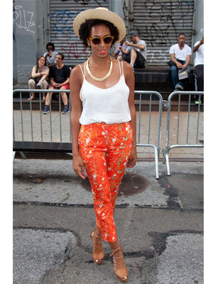Solange Knowles sports a very vibrant and relaxed summery look. The holiday look was worn as a statement to Kim Jones' fashion party in New York; the bright orange trousers somewhat separates her look from her older sisters sense of style!