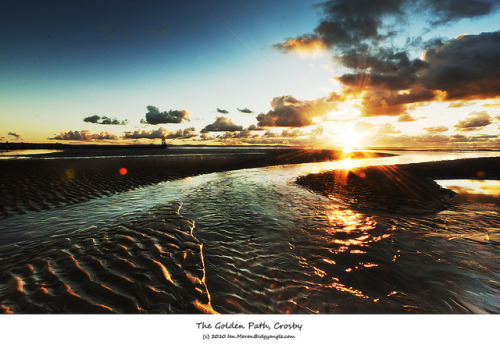 The Golden Path, Crosby on Flickr.A shot from my muddy boots evening at Crosby beach last year.  Have pushed the processing to bring out a little more drama for this one, I like the contrast of both colour and light, and the snake of water leading you out to sea with the windfarm to the right of frame, hope you find it agreeable. Have a great day.