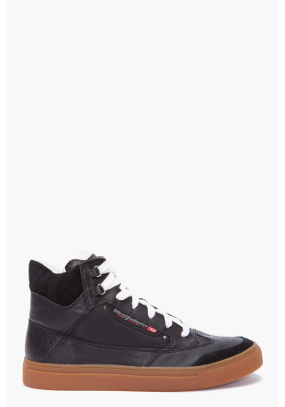 Claw king Sneakers by Diesel. High top leather and suede sneakers in black. Round perforated wing tip toe. White lace up tie with silver tone d rings at top. Logo embroidery at padded tongue. Logo flag and gunmetal rivets at outer side. Padded top line. Tone on tone stitching. Brown rubber sole with logo imprints and textured foxing.More…
