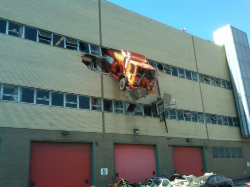 FDNY tweeted this photo of a garbage truck dangling two-stories high from a sanitation garage in Queens.  Firefighters rescued the driver.