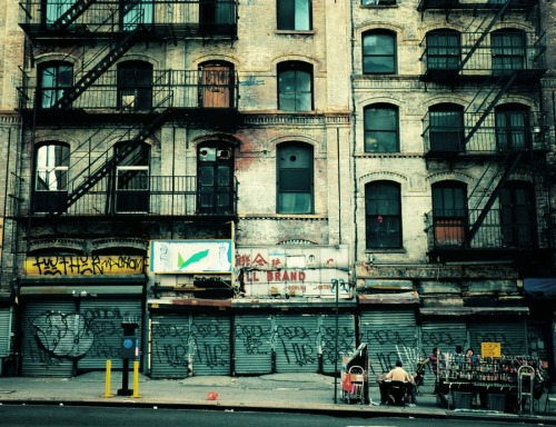 "Urban decay. Chinatown, New York City.  New York City changes and evolves at a rapid pace. In certain areas, changes occur faster than others. Lower Manhattan is one place that has changed the most in the last decade. Development happens fast and the current trends are extremely tall buildings constructed mostly of glass, chain stores and luxury boutiques. In neighborhoods that were once bohemian and home to artists and rebels, these current changes have been hard to swallow for long-time residents who run the risk of being out-priced out of the neighborhoods they have called home for decades.  Despite these changes, there are still parts of lower Manhattan that recall earlier decades. New York City suffered economically in the 1970s and it was during this decade that much of lower Manhattan was transformed into a danger zone full of abandoned lots and buildings and rampant crime. Having grown up in New York City in the 1980s and early 1990s, I have vivid memories of riding graffiti-covered trains from Queens into Manhattan. I was taught to 'watch my back' at all times since everyone seemed to know someone who had been mugged. Things were still different in those days prior to the initiatives by mayors Koch and Guiliani to 'clean up' the city (and discourse is still rampant regarding how they handled it).   When I came across this section of Canal Street while walking home from getting groceries a few months back, my heart almost leaped out of my chest. Here I was staring at a section of a spot in Chinatown that seemed as if it had been dipped in 1980s New York City and had become frozen in time (thankfully I had my camera). It's hard to put into words how powerful this scene is for personally. It's a bit like staring at something that once existed in a distant life.   A city may change rapidly discarding pieces of itself, but it's the people who carry it's broken pieces with them in their hearts who imbue the city with its memory.    —-  View this photo larger and on black on my Google Plus page  —-  Buy ""Decay"" Posters and Prints here, View my store, email me, or ask for help."